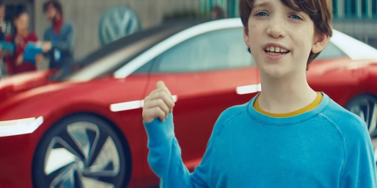 Junge zeigt auf ein rotes Auto