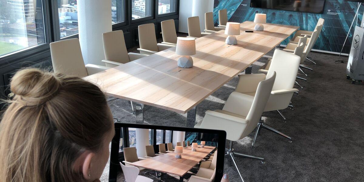 Frau projiziert einen Sessel in einen Konferenzraum