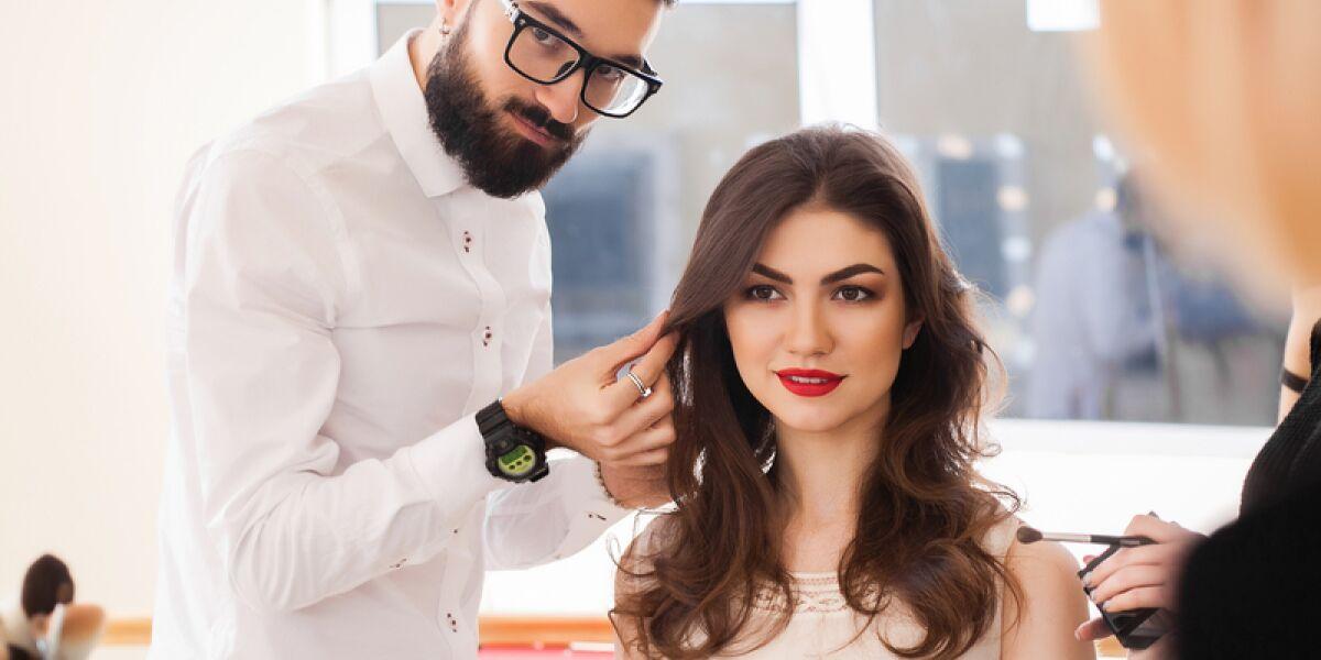 Mann stylt einer Frau die Haare