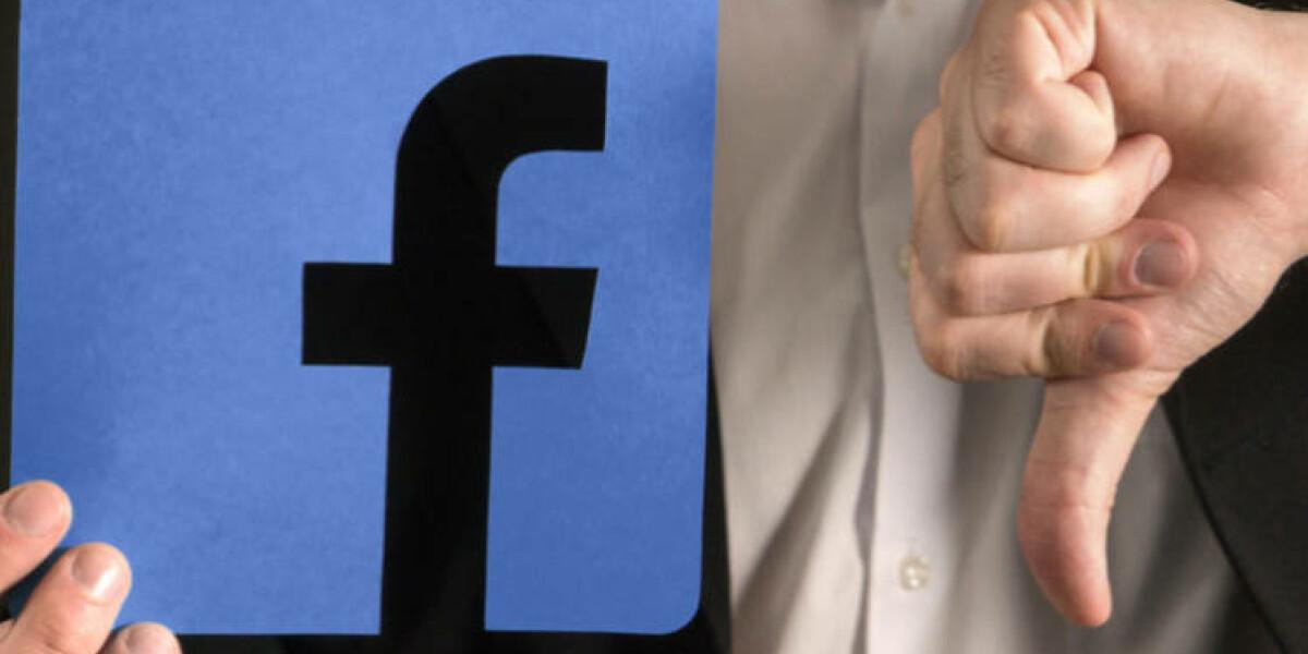 Mann hält Facebook-Symbol mit Daumen nach unten