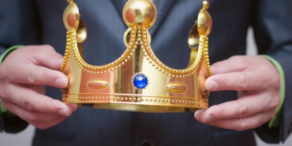 Geschäftsmann trägt Krone in den Händen