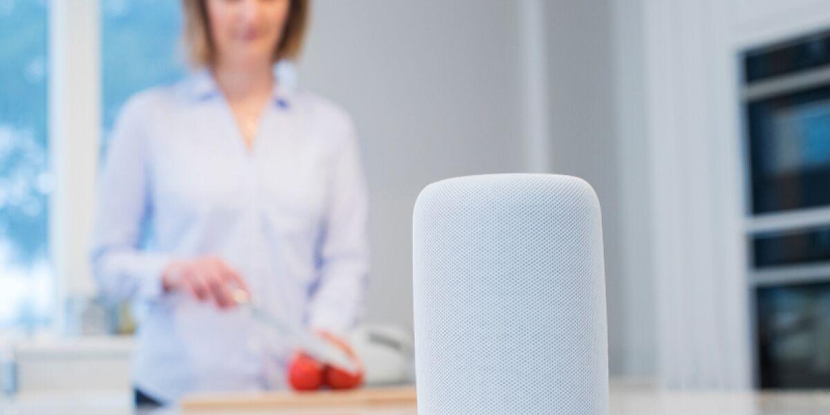 Frau in der Küche mit einem smarten Speaker