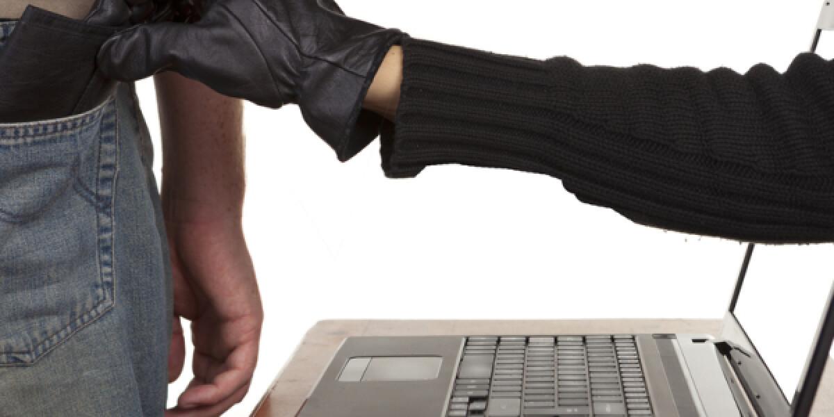Hand zeiht durch Laptop Mann Geld aus der Tasche