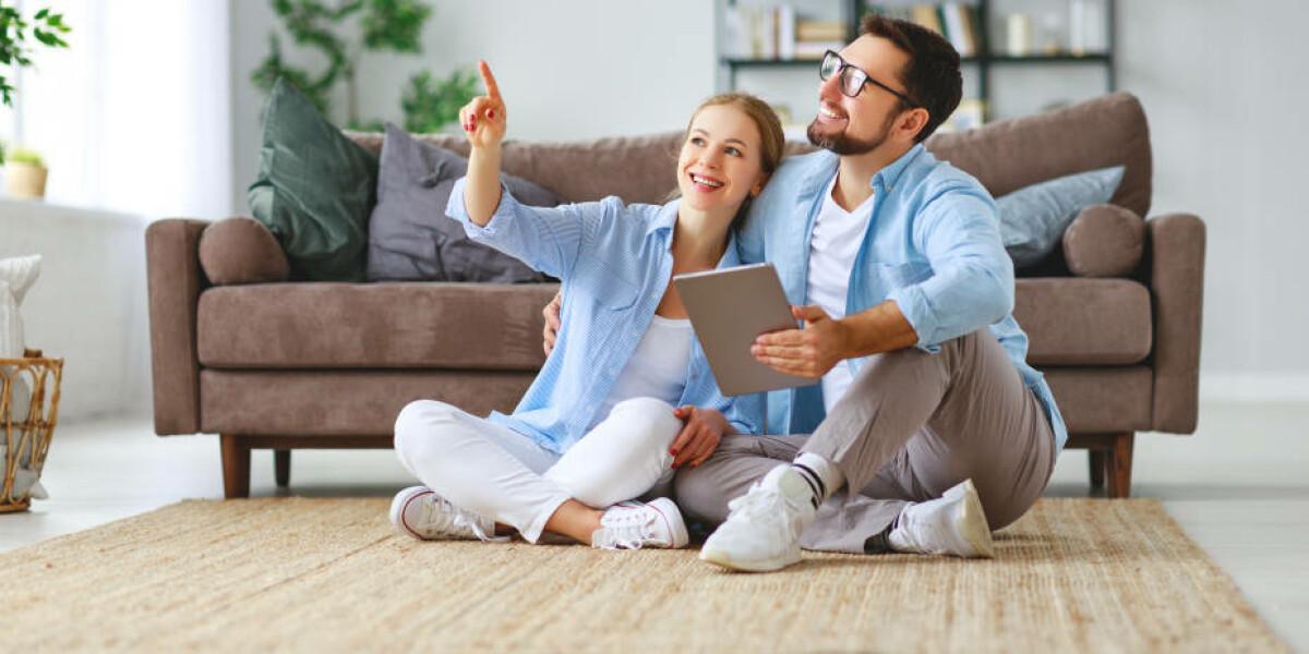Paar sitzt mit Tablet im Wohnzimmer