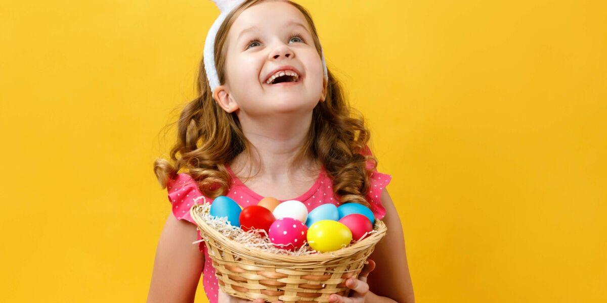 Kind hält einen Korb mit Ostereiern