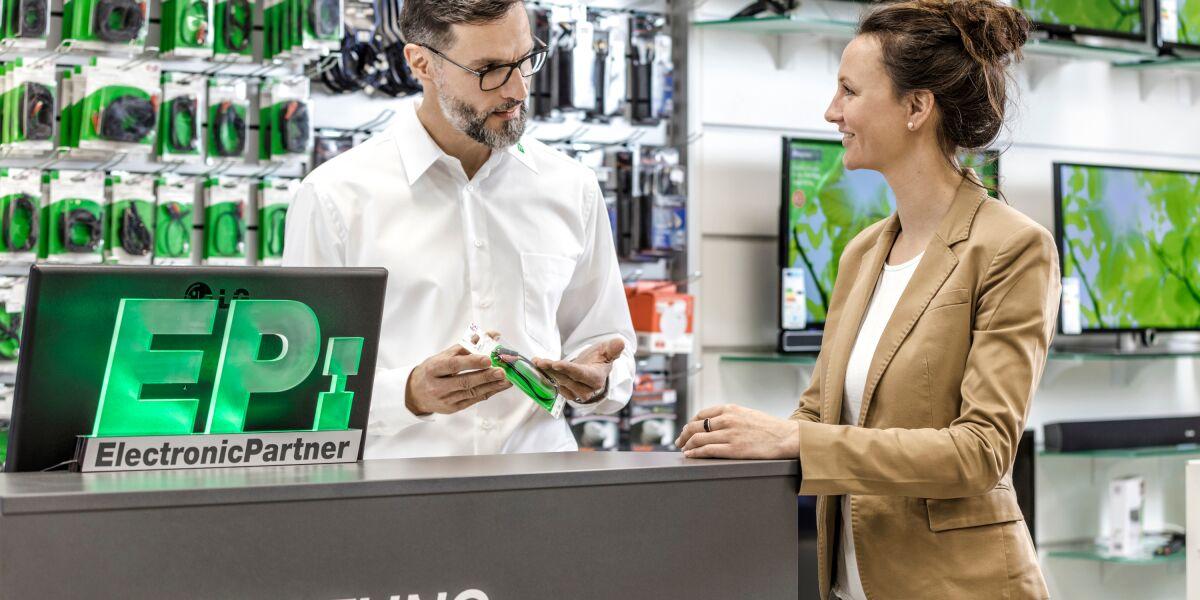 Mann berät eine Frau in einem Laden