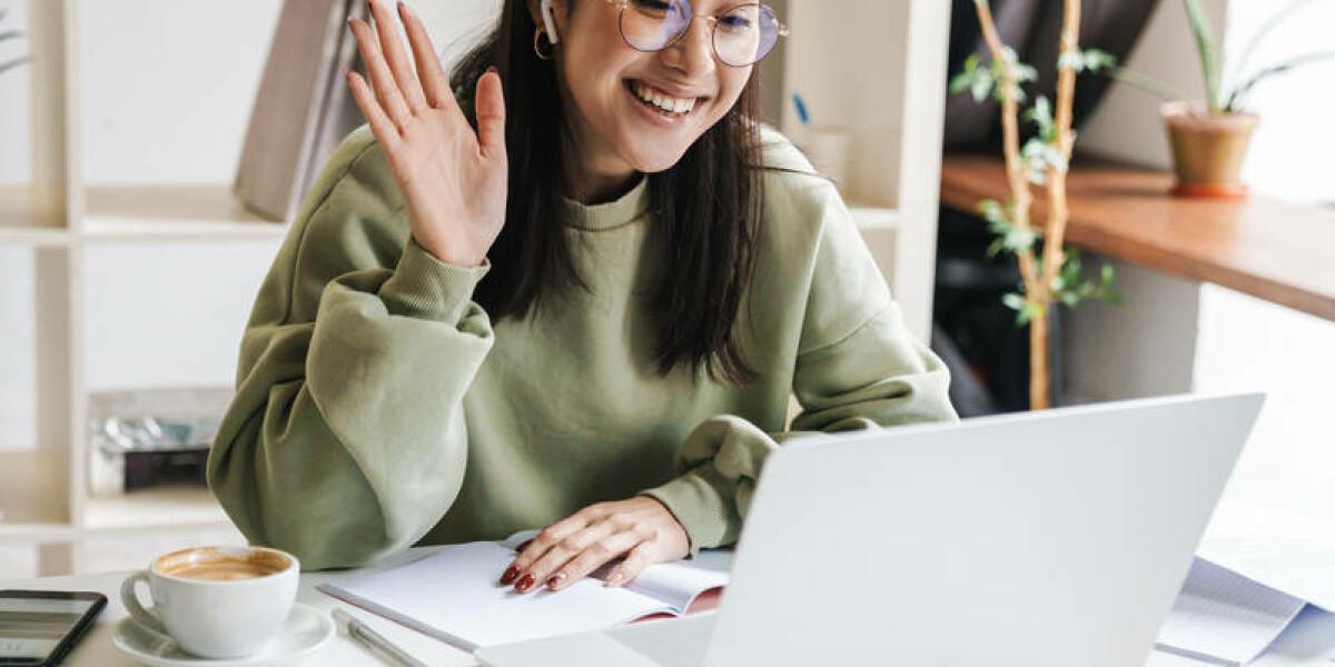 Frau winkt in die Laptop-Kamera