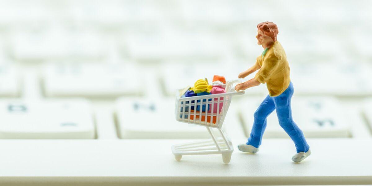 Figur mit Einkaufswagen auf einer Tastatur