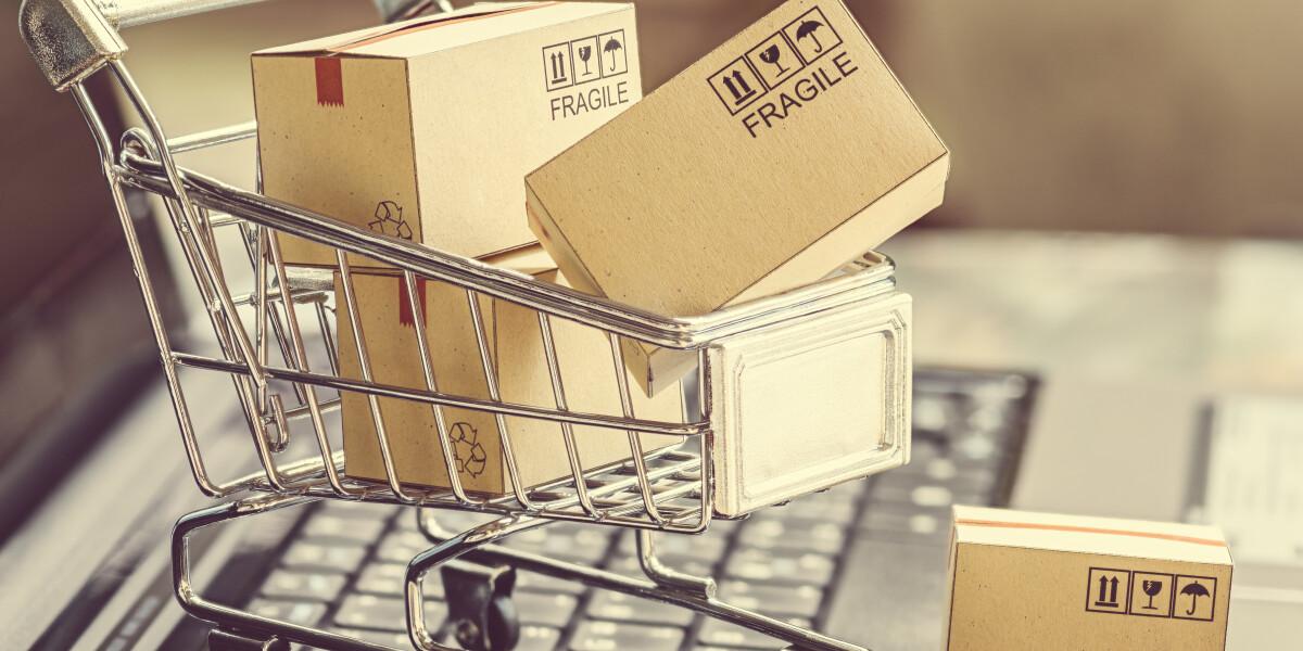 Einkaufswagen mit Paketen auf einem Laptop