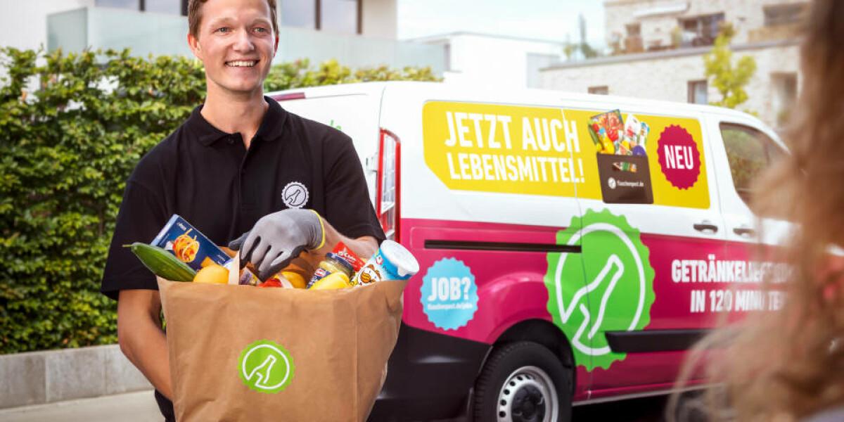 Mann trägt Lebensmittel von Auto zu Haus der Kundin
