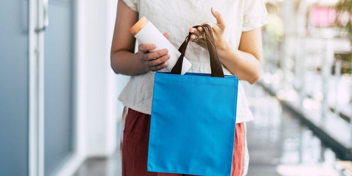 Frau steckt Plastikflasche in Einkaufstasche