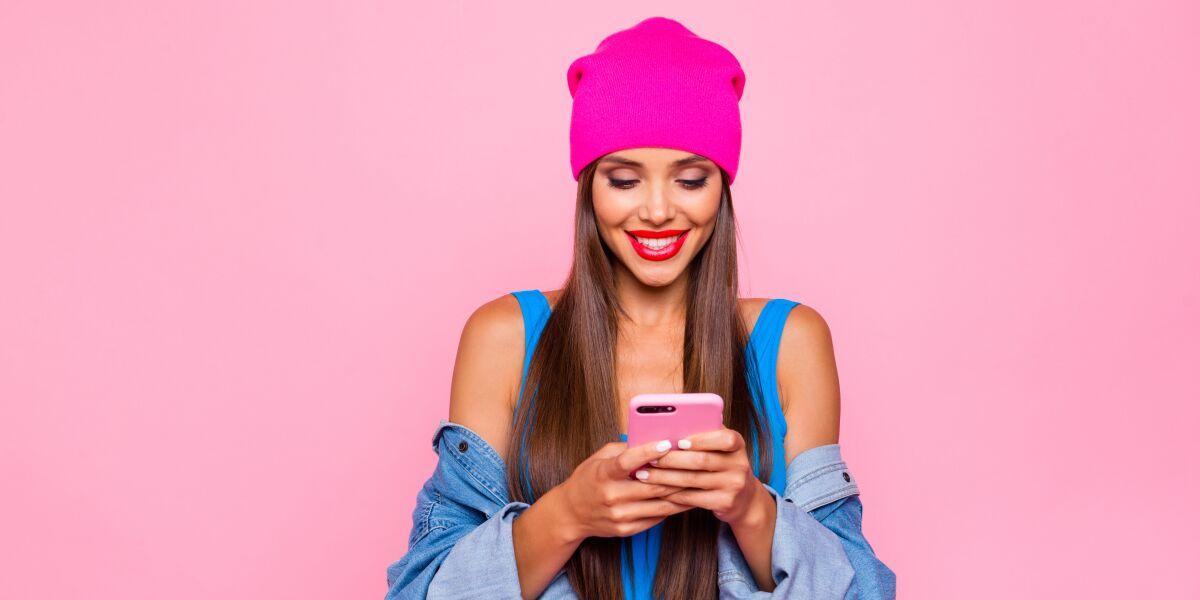 Smartphone junge Dame pinke trendy Mütze knallroter Lippenstift