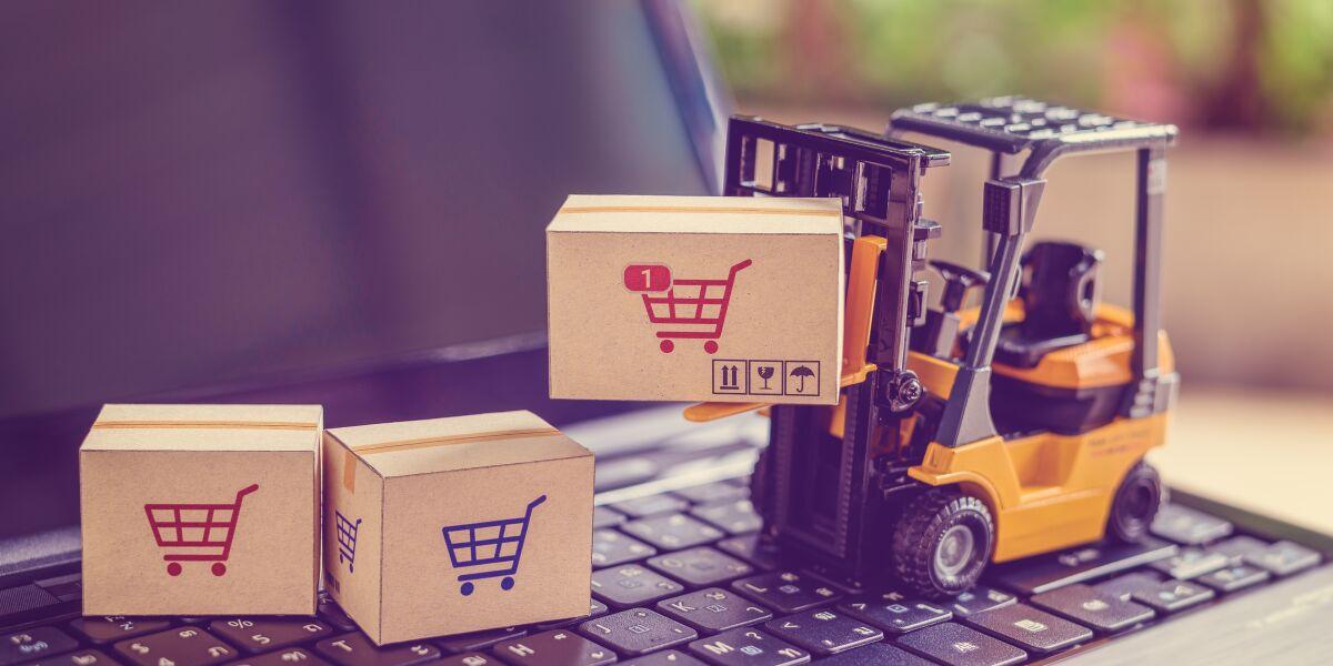 Pakete mit Warenkorb-Symbol werden von Gabelstapler über Laptop transportiert