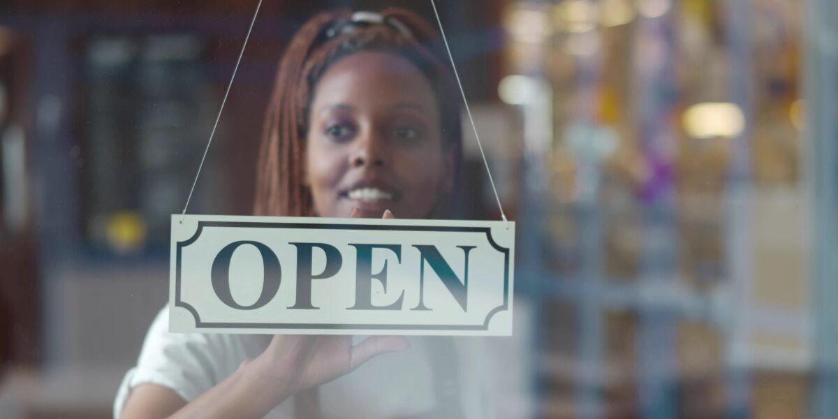 geöffnetes Geschäft mit Besitzerin