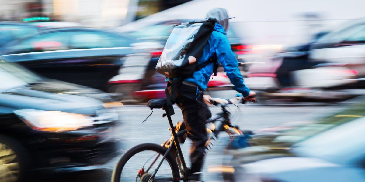 Fahrradbote im belebten Stadtverkehr