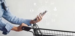 Frau mit Einkaufswagen und Smartphone inklusive Multichannel-Icons