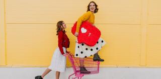 Mädchen posieren mit Herzsymbol und Einkauswagen