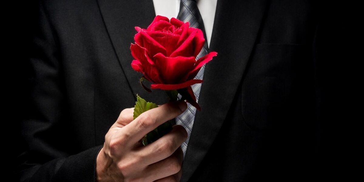 Nahaufnahme eines Mannes in schwarzem Anzug, der eine rote Rose hält.