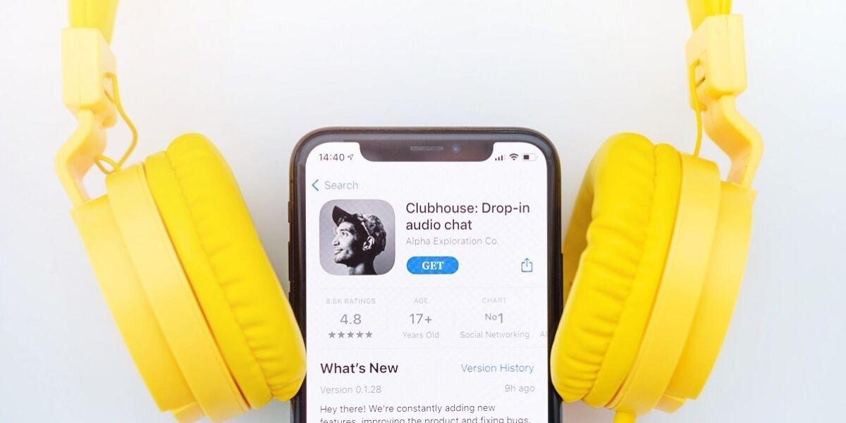 Clubhouse-App auf Smartphone mit gelben Kopfhörern