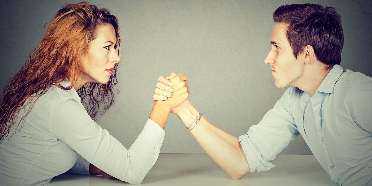 Mann und Frau beim Armdrücken