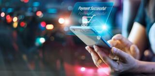 Frau hält Smartphone in der Hand und tätigt Online-Zahlung