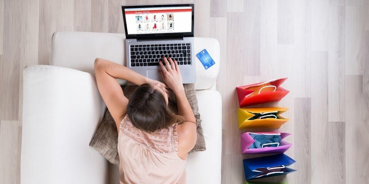 Junge Frau auf Sofa beim Online-Shopping mit Laptop