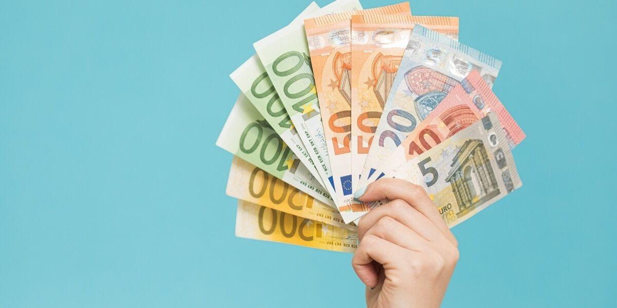 Hände, die Euro-Banknoten auf blauem Hintergrund halten.