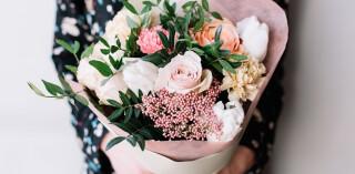 Frau, die einen blühenden Blumenstrauß hält