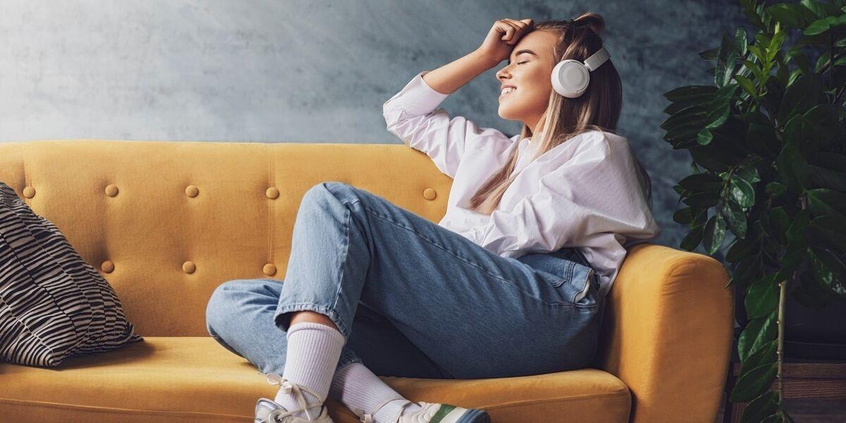 Frau mit Kopfhörern auf gelbem Sofa