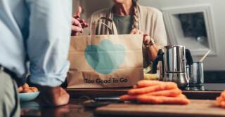 Eine Too Good To Go-Tüte auf einem Küchentisch mit Karotten
