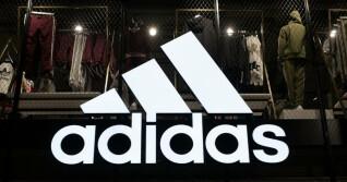 Adidas Logo vor Produkten im Hintergrund