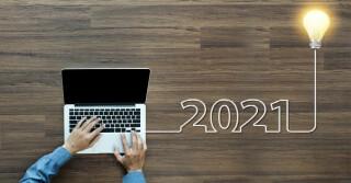 Laptop auf Holztisch, 2021 Schriftzug und Glühbirne