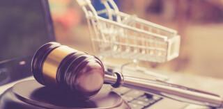 Hölzerner Richtergavel und Einkaufswagen auf einem Laptop