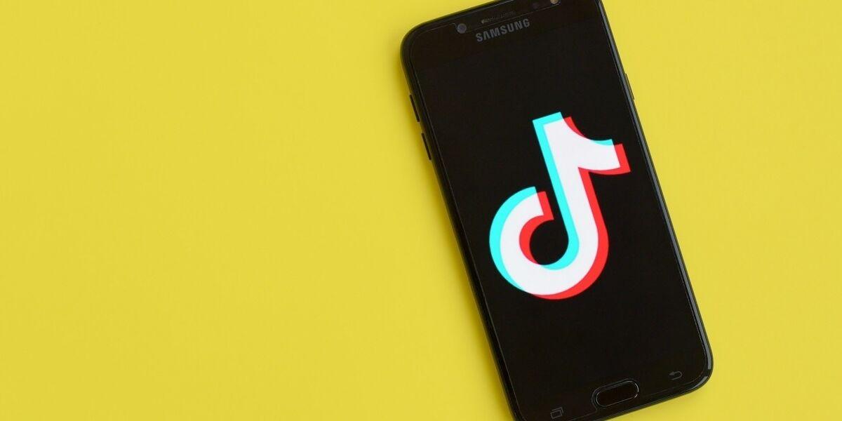 TikTok Symbol auf Smartphone-Screen vor gelbem Hintergrund