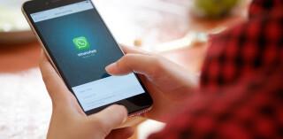Person hält Smartphone in der Hand und nutzt Whatsapp