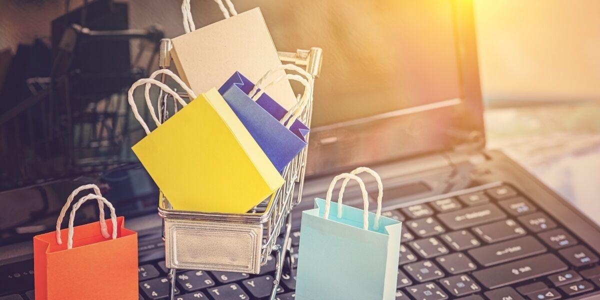 Farbige Papiereinkaufstaschen in einem Trolley auf Laptop-Tastatur.