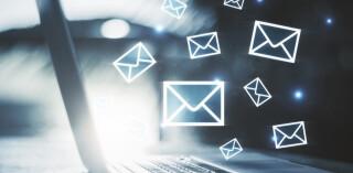 Seitenansicht eines Laptops mit E-Mail-Symbolen