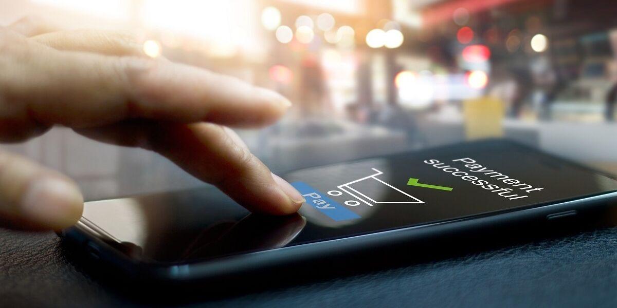 Hand vor Smartphone-Screen, der Zahlungsbestätigung anzeigt