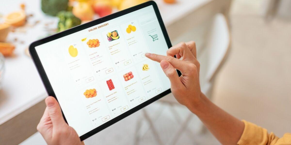 Person kauft Lebensmittel online mit Tablet