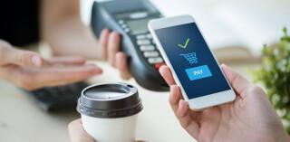 Person bezahlt Kaffee per mobile Payment