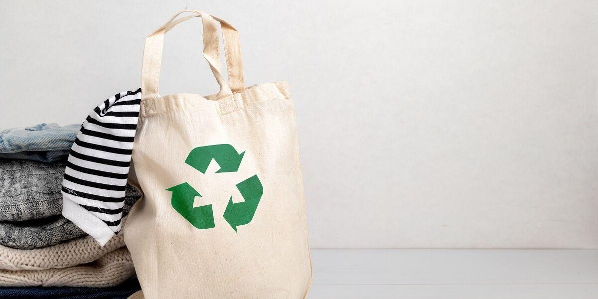 T-Shirt-Stapel und Beutel mit Symbol für Recycling