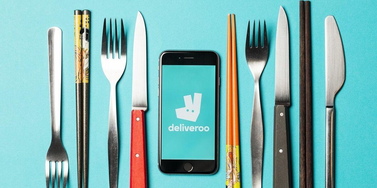 Smartphone mit Deliveroo-App und Besteck
