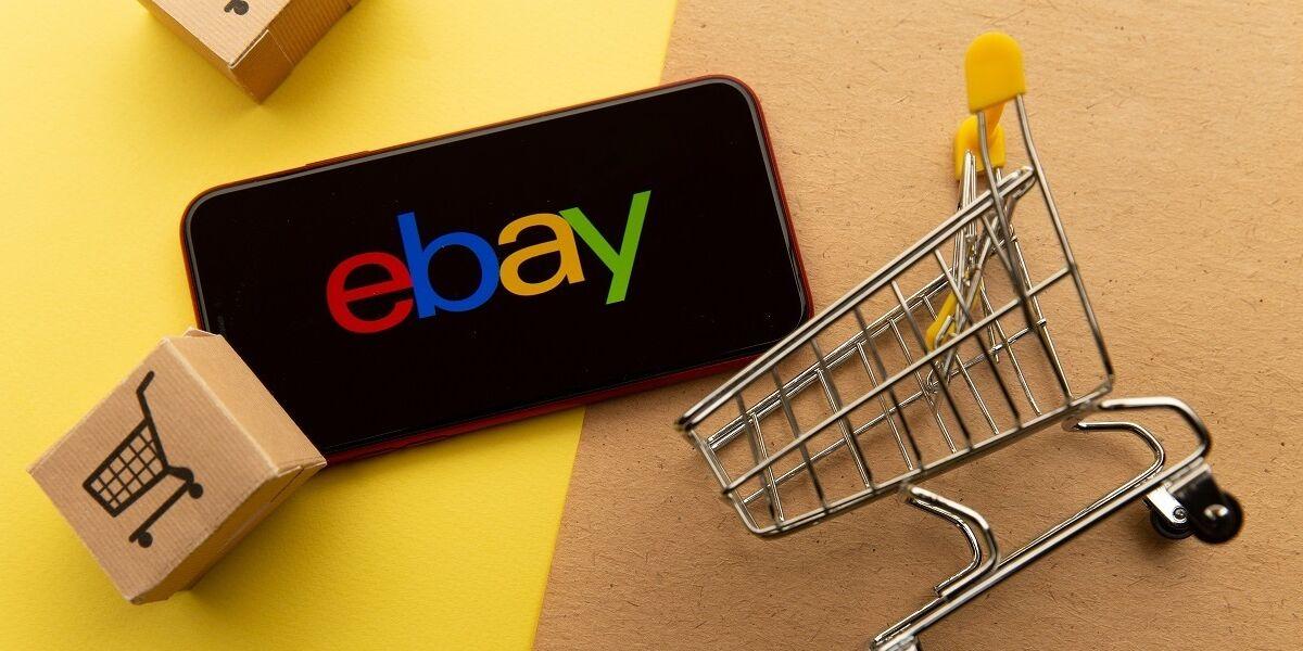 Ebay Logo auf Smartphone Screen, daneben Pakete und Einkaufswagen