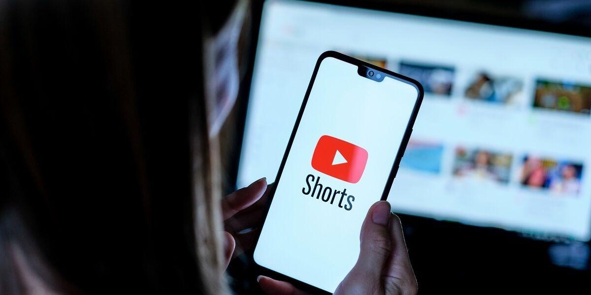 Person hält Smartphone mit Youtube Shorts App Logo