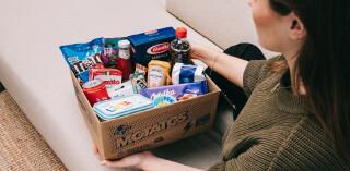 Frau auf Couch mit Karton voller Lebensmittel