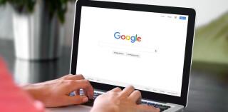 Person vor Laptop mit Google-Suche