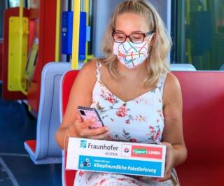 Frau in Tram mit Paket