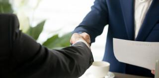 Männer geben sich bei Vertragsabschluss die Hand