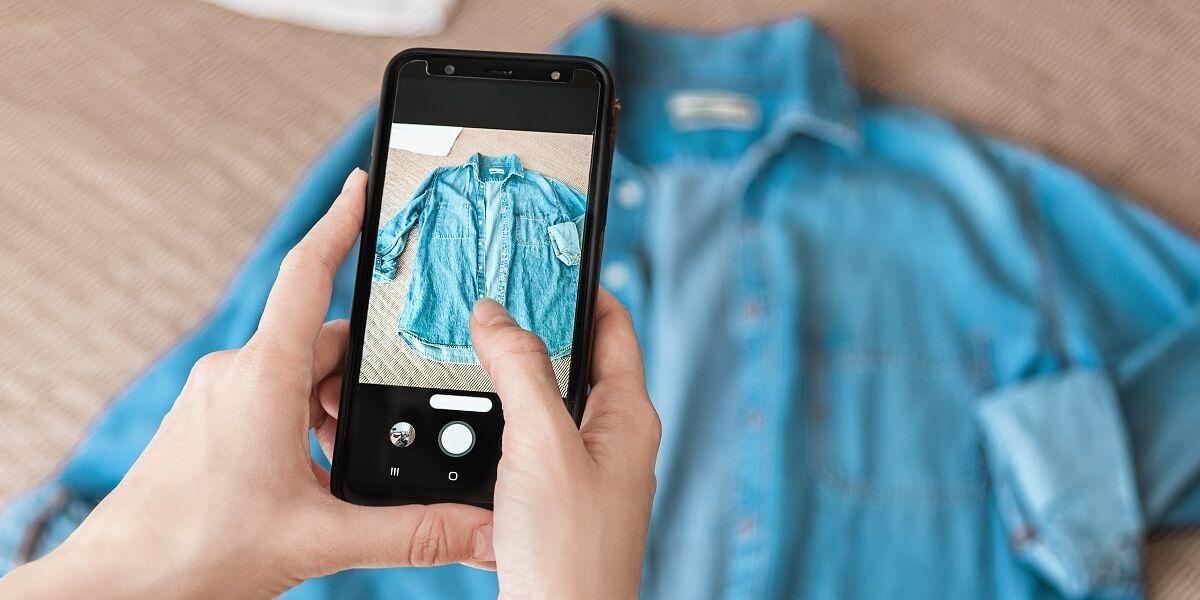 Person fotografiert Denim-Shirt auf Smartphone