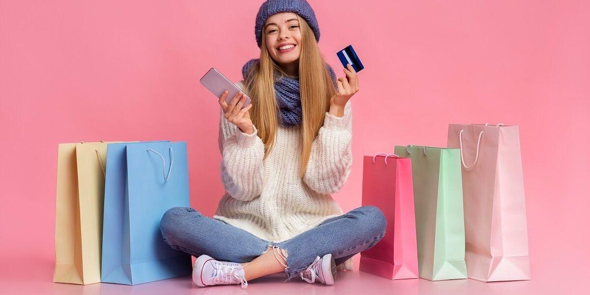Frau zwischen Einkaufstaschen sitzend beim Online-Shopping